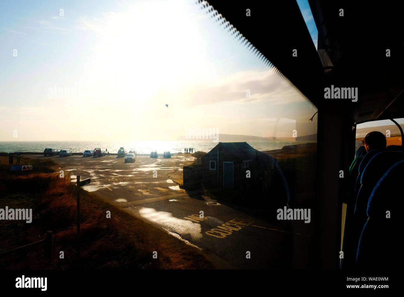 Passenger view from a bus window on the upper deck of evening sunshine over the sea Stock Photo