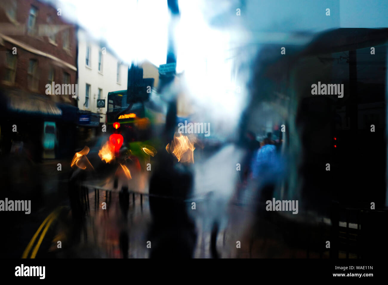 Passenger's view of blurry pedestrians out of bus window on wet rainy day with water running down the bus window pane Stock Photo