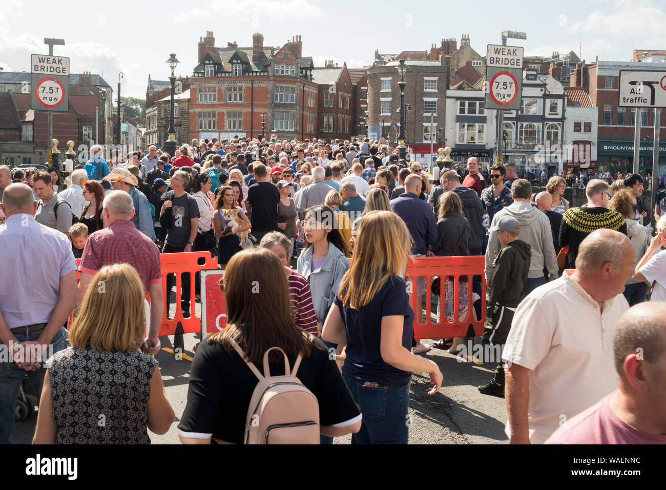 Crowds of people crossing the swing bridge during Whitby folk festival, North Yorkshire, England, UK Stock Photo