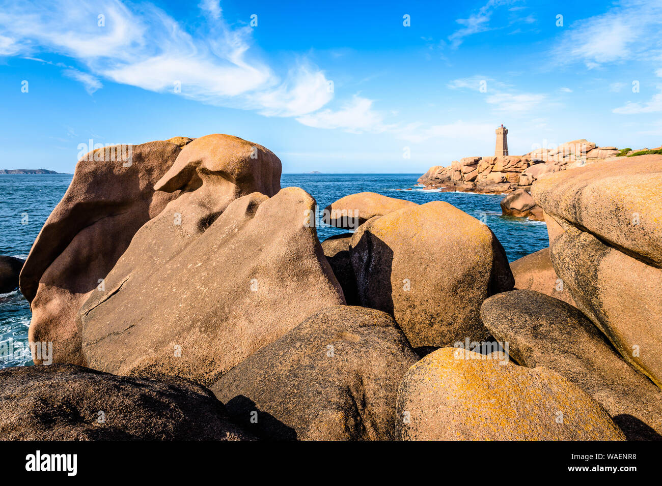 The Ploumanac'h lighthouse, named Mean Ruz, on the Pink Granite Coast in Perros-Guirec, northern Brittany, with large granite rocks in the foreground. Stock Photo