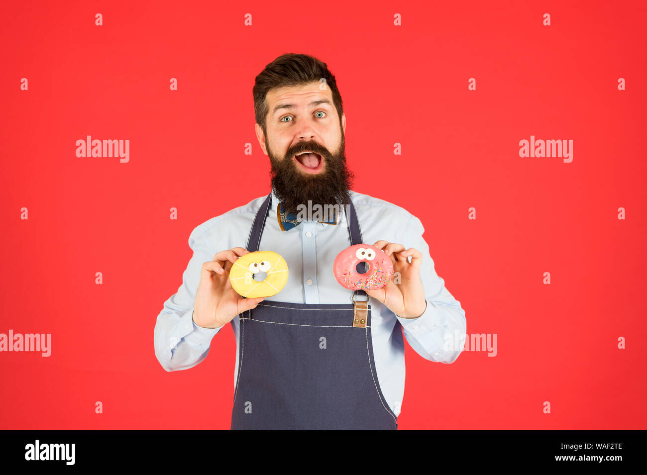 Junk food  Hipster bearded baker eat donuts  Doughnut bakery