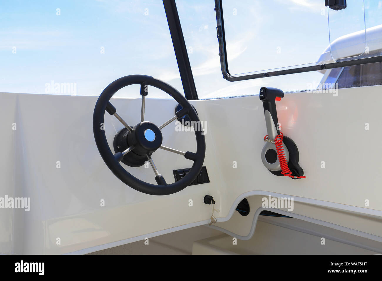 Motor boat steering wheel with throttle control in cockpit Stock Photo