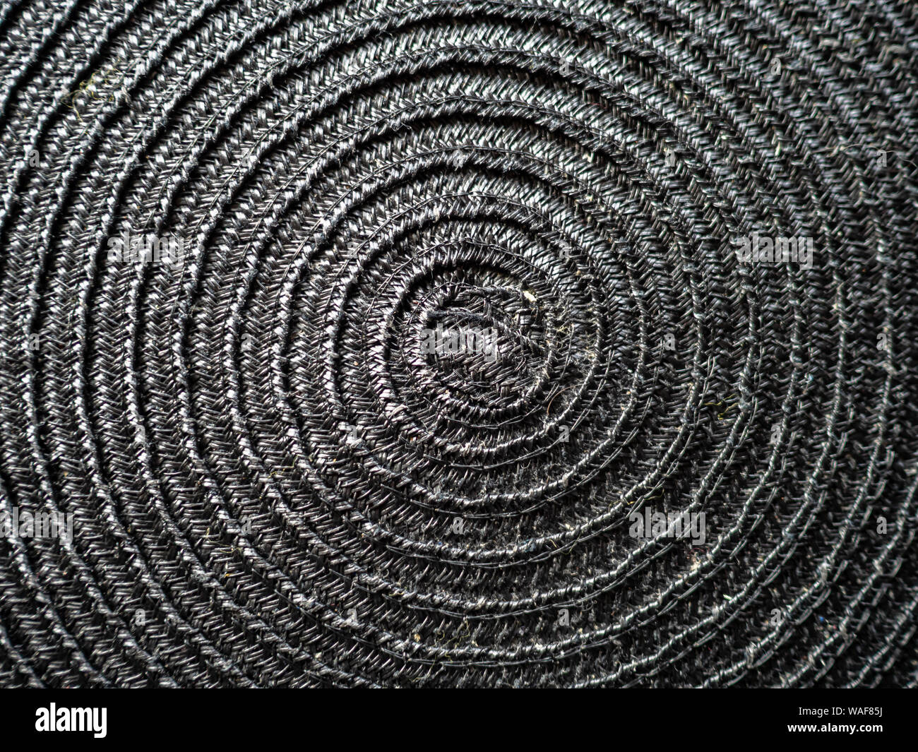 Detail of a black placemat, woven from natural materials featuring concentric spiralling circles Stock Photo