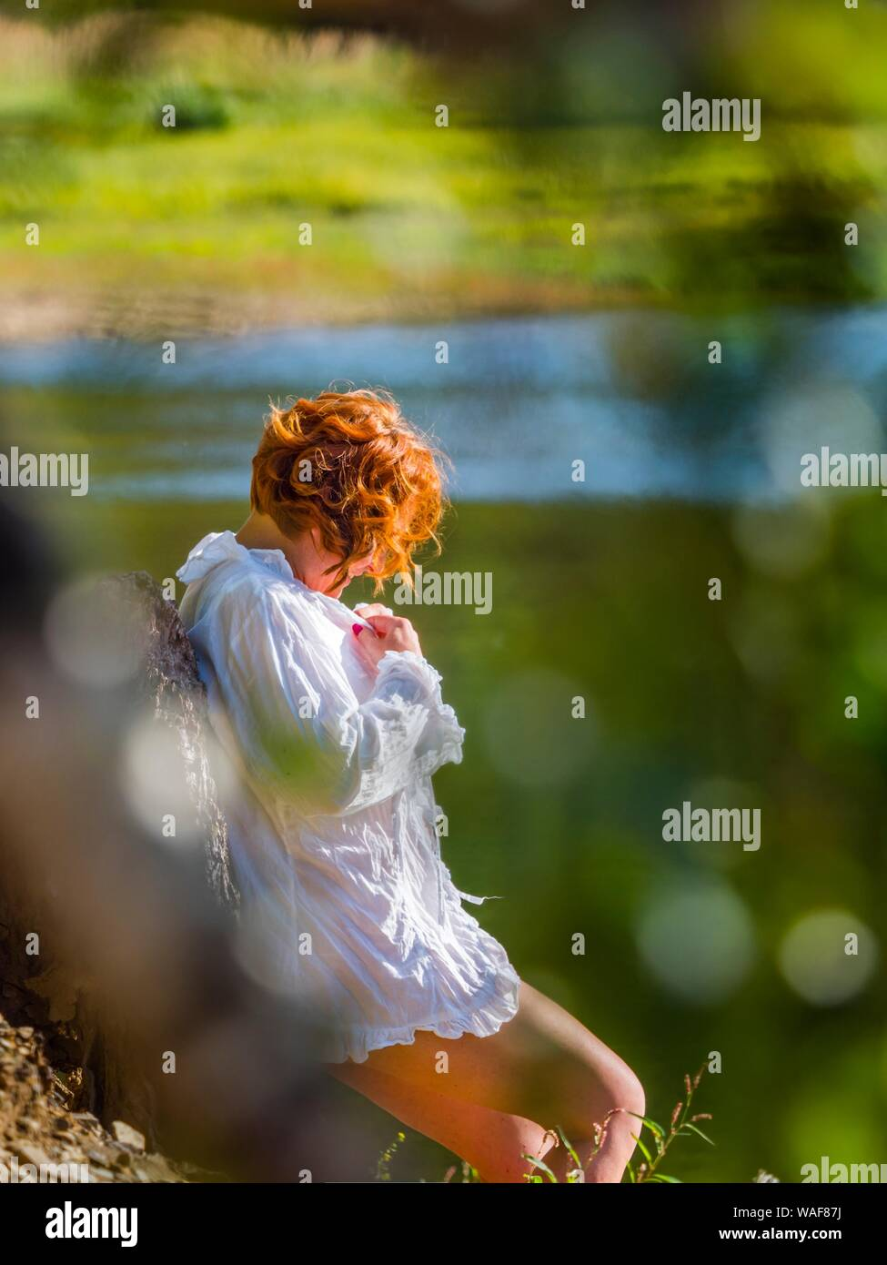 Attractive woman in nature enjoying sun sunlight sunlit isolated from background bokeh aka stalked by voyeur through tree branches leaves vegetation Stock Photo