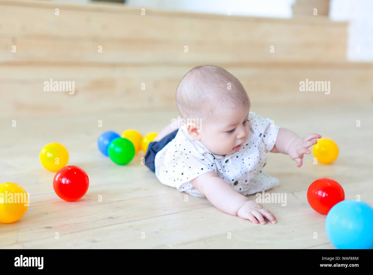 Baby boy playing with balls. Colorful toys for kids. Kid in play room. Toddler kid with balls  for children. Stock Photo
