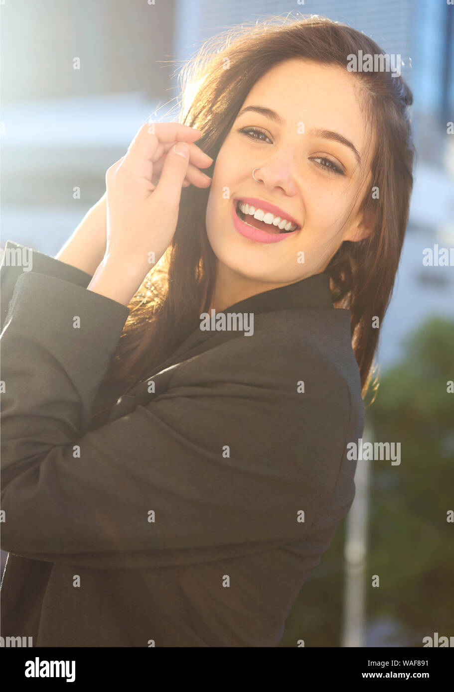 Young woman in jacket standing on balcony with city background at sunset. Sexy attractive woman with fashion styling Stock Photo