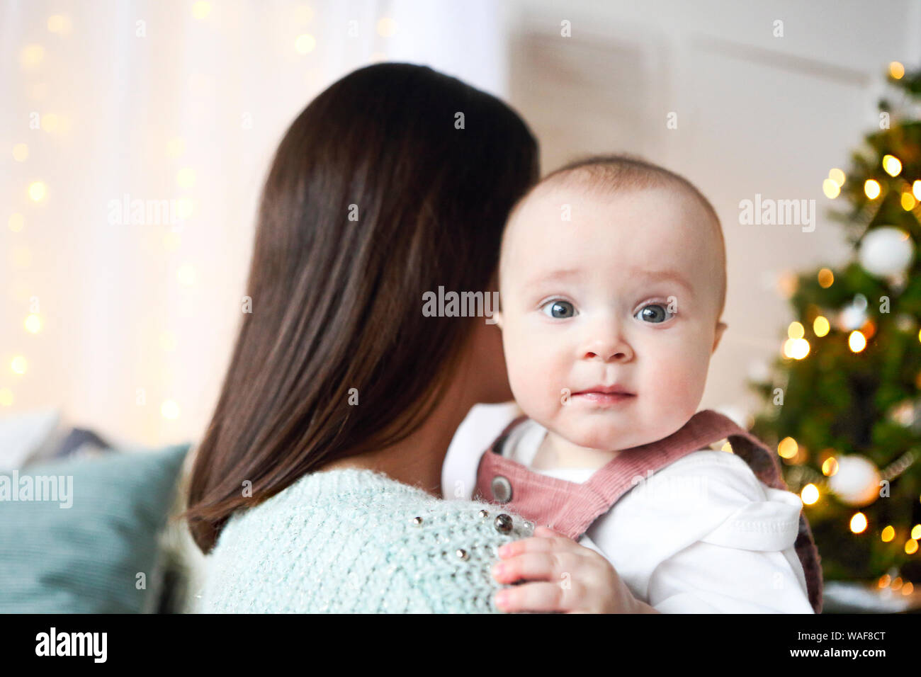 Beautiful happy mother with lher ittle daughter in knit sweater sitting on the background of Christmas interior hugging together and smiling Stock Photo