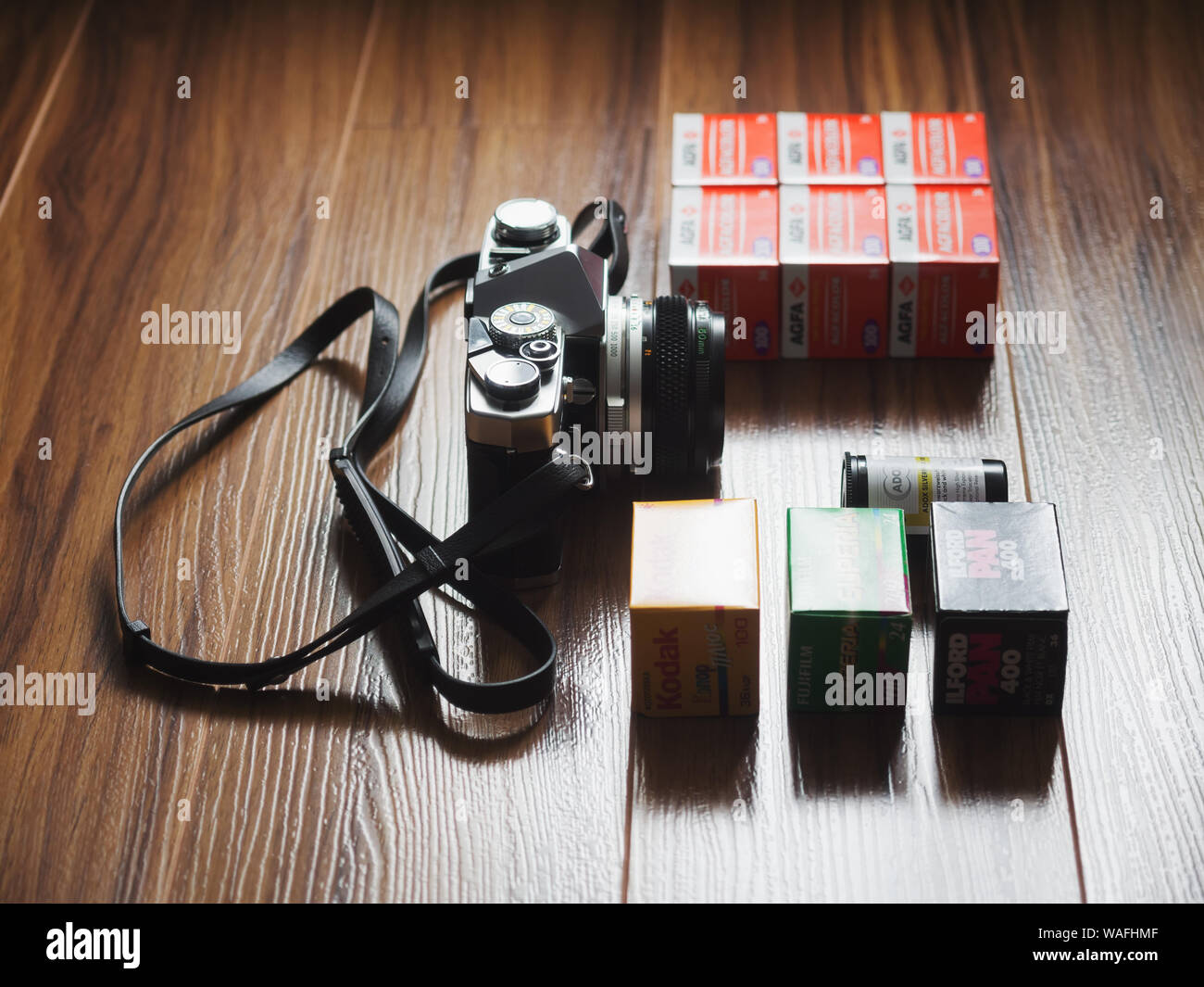 Moscow, Russia - June 17, 2016: Analogue Photography. Fujifilm, Agfacolor, Kodak, ILFORD and Adox 35mm film rolls and vintage Olympus OM-1 SLR camera Stock Photo