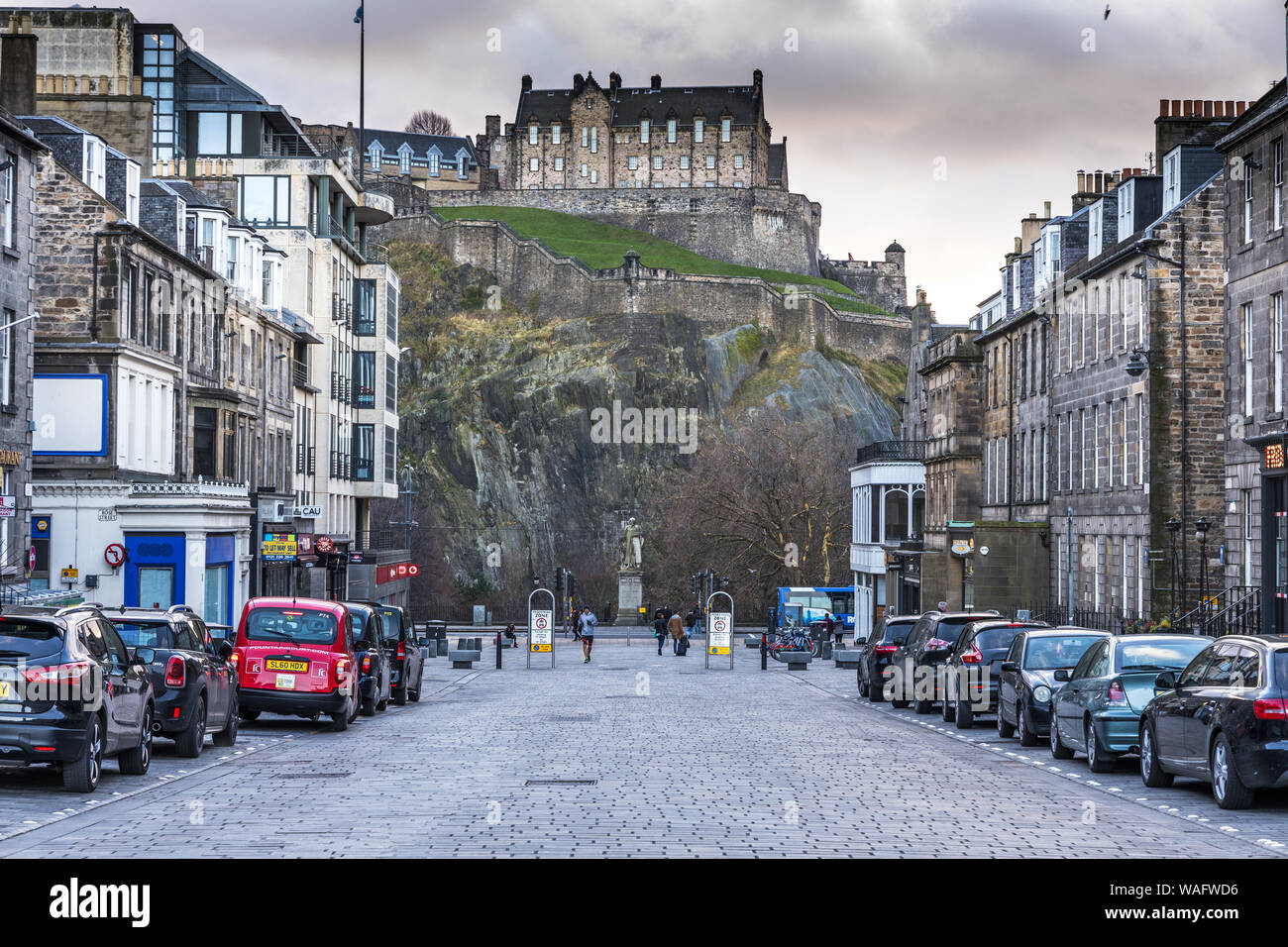 Cobbled street view looking towards the  Statue of Thomas Guthrie on Princes Street with the Castle above Edinburgh Scotland Stock Photo