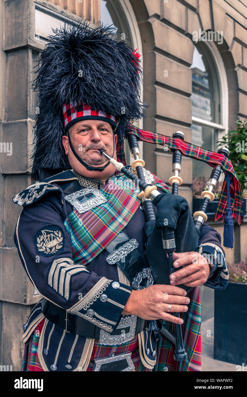 Close up head and shoulders of a Scottish bagpiper playing pipes in full uniform Edinburgh, Scotland Stock Photo