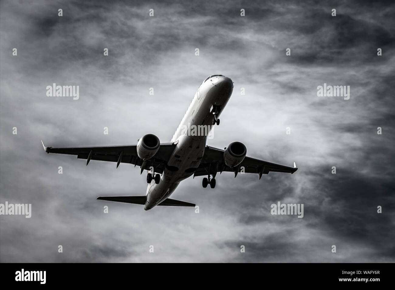 Airplane landing in front of dramatic sky in black and white Stock Photo