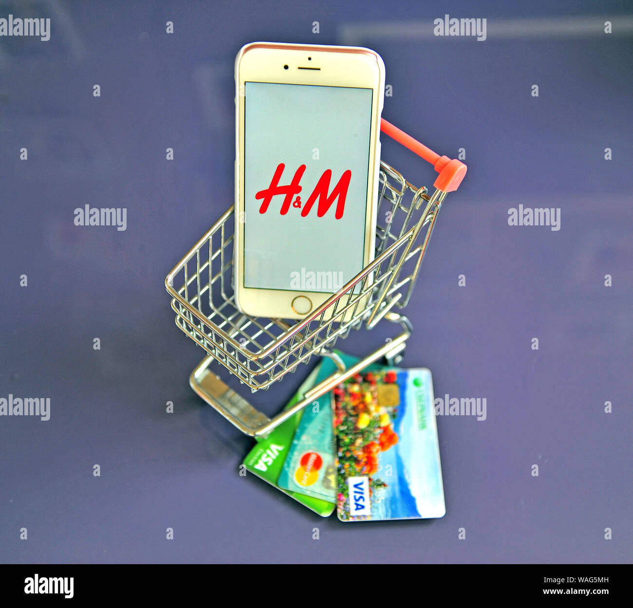 Yaroslavl, Russia - AUgust 20, 2019: Smartphone with H&M logo in shopping cart and credit cards on the table. Stock Photo