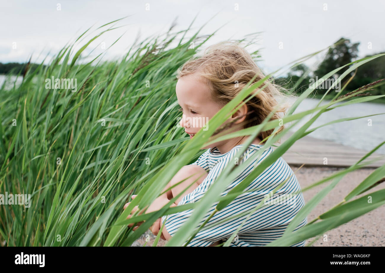 portrait of a young girl sitting smiling at the beach in summer Stock Photo
