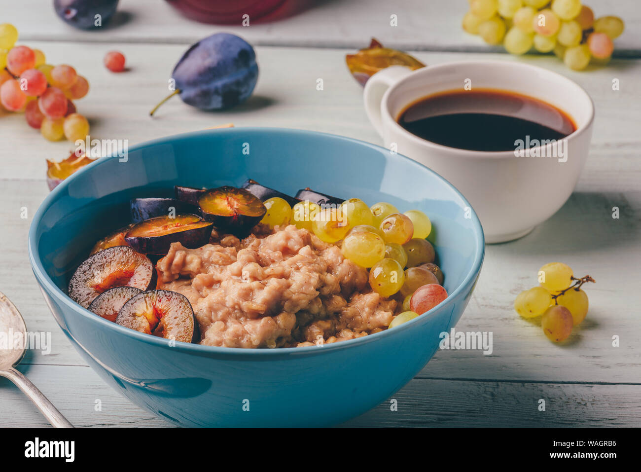 Healthy breakfast concept. Porridge with fresh plum, green grapes and cup of coffee. Ingredients over wooden background. Stock Photo