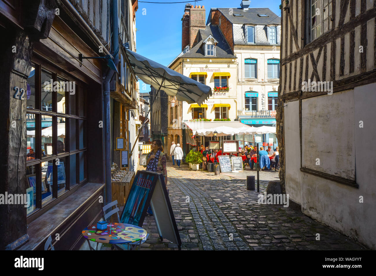 A Woman Window Shops On A Sunny Day In The Normandy Town Of Honfleur France With An Outdoor Sidewalk Cafe Behind Her Stock Photo Alamy