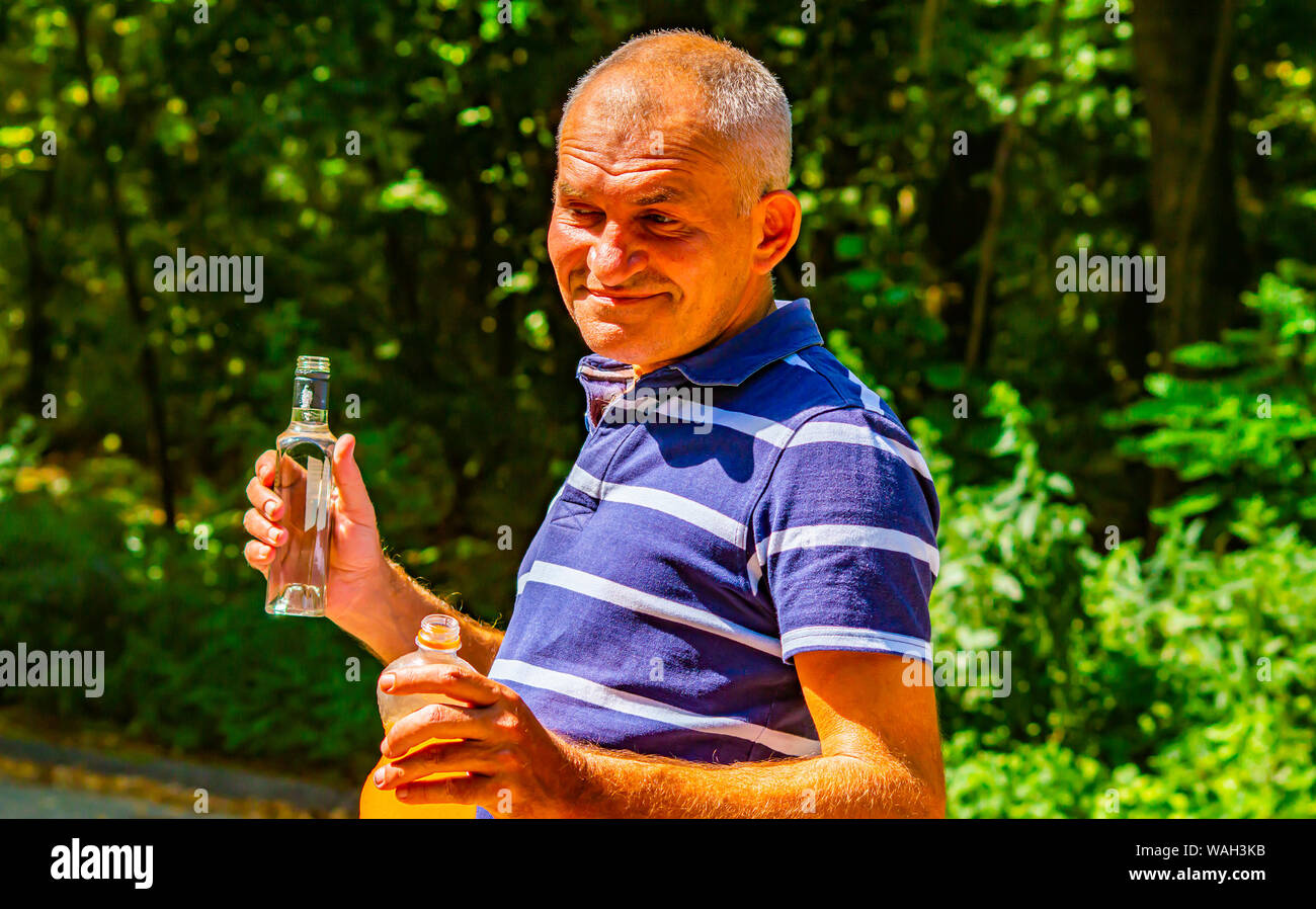 A man with a bottle of vodka in his hand  Alcoholism  Social