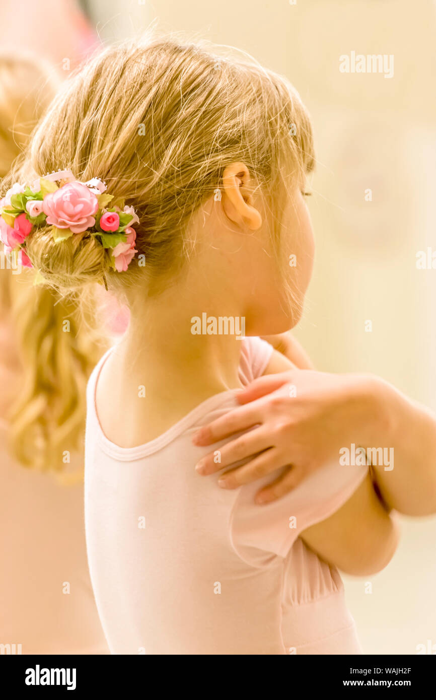 Rear view portrait of a six year old girl ballet dancer hugging herself, who is wearing a floral ballet bun hairpiece, in a dance studio. (MR) Stock Photo