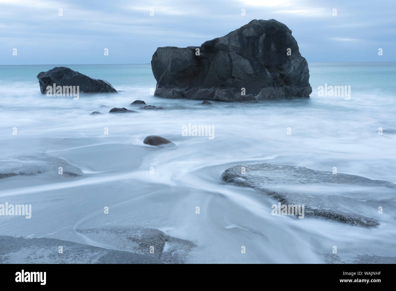 Norway, Lofoten Islands, Vestvag Island, Leknes. Here on the western side of Vestvag Island, the dark rocks contrast with the white water. Stock Photo
