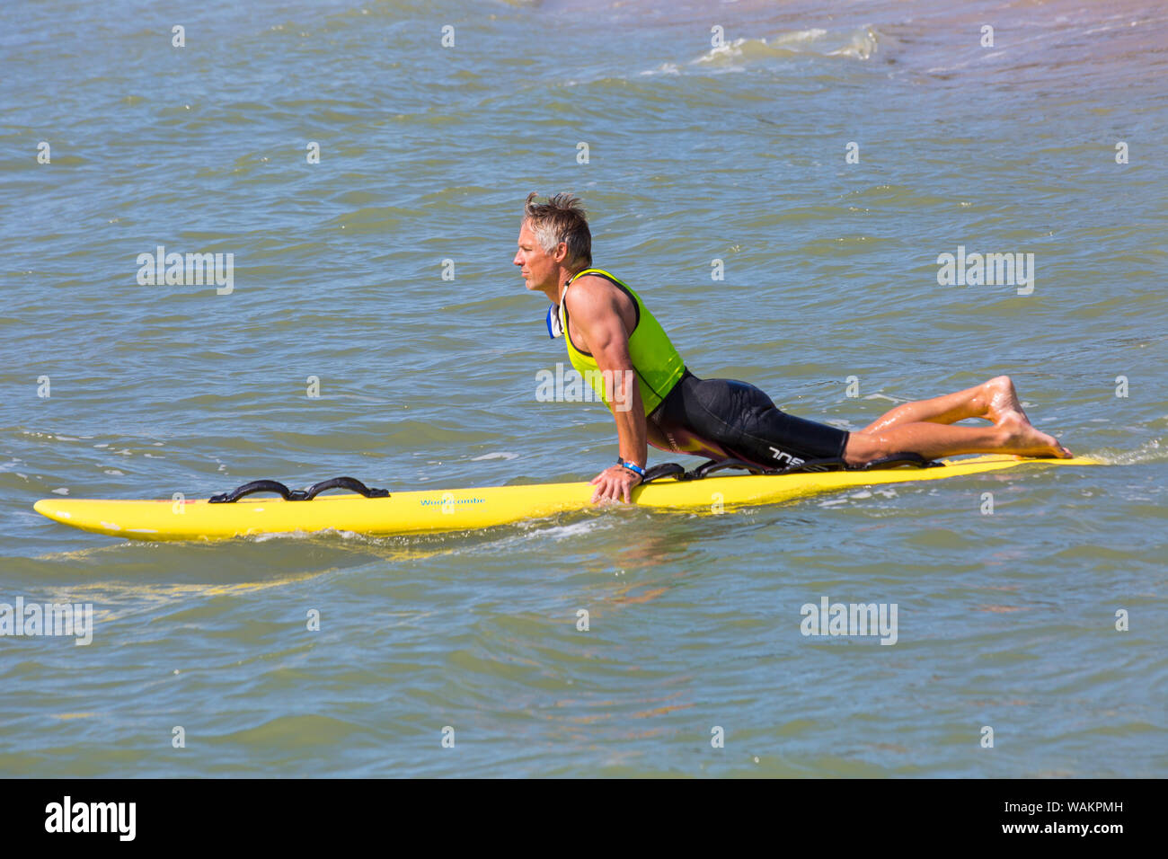 Lifeguard with surf board at Branksome Chine, Poole, Dorset UK on a warm sunny day in August Stock Photo