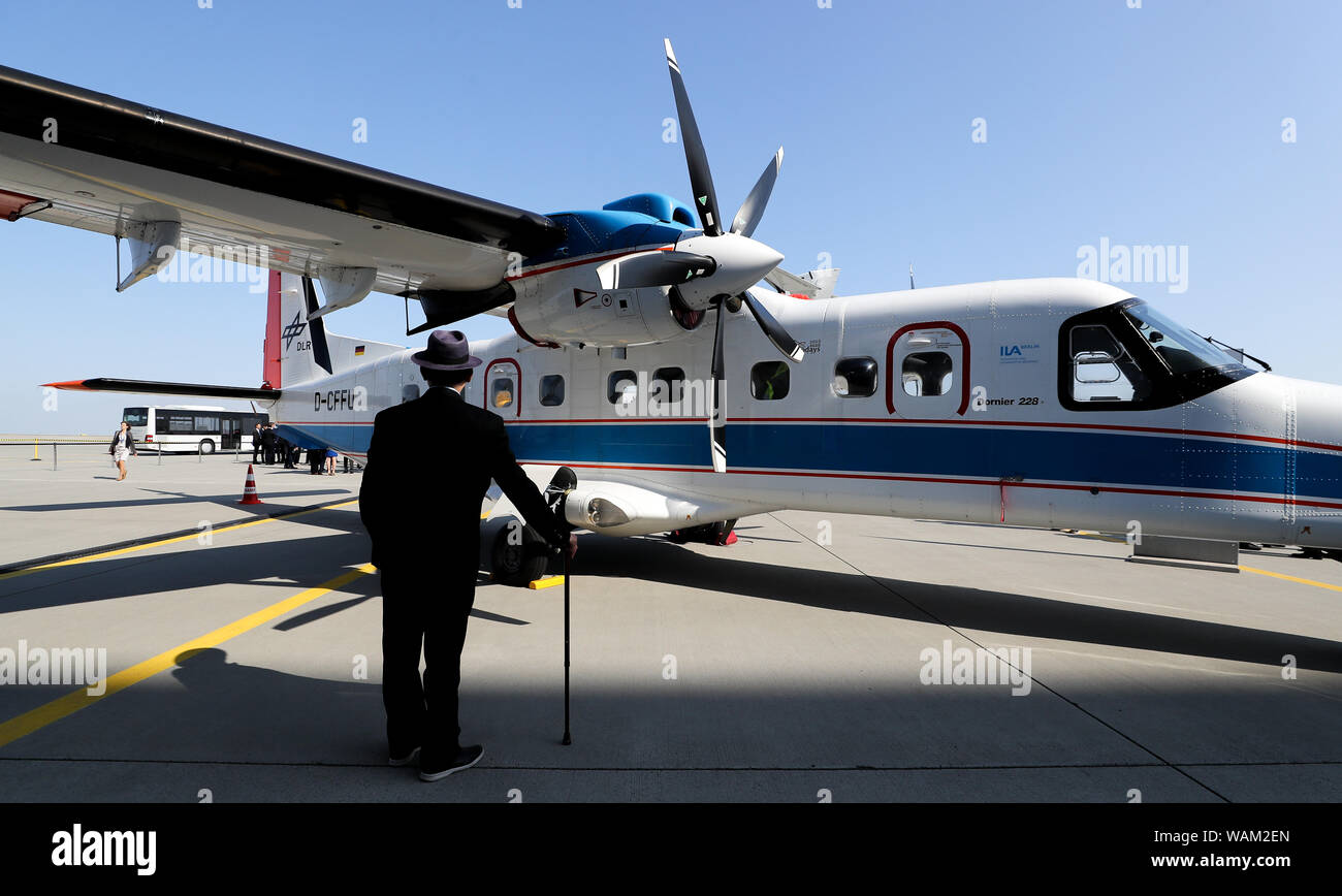 Schkeuditz, Germany. 21st Aug, 2019. A foreign guest of the National Aviation Conference is standing in front of an electric test aircraft (Dornier 228) at Leipzig-Halle Airport. Guiding principle of the conference: The German aviation industry should become more competitive and at the same time more environmentally friendly. Among those expected are the German Chancellor, the ministers of transport and economics, and the Lufthansa CEO. Credit: Jan Woitas/dpa-Zentralbild/dpa/Alamy Live News Stock Photo