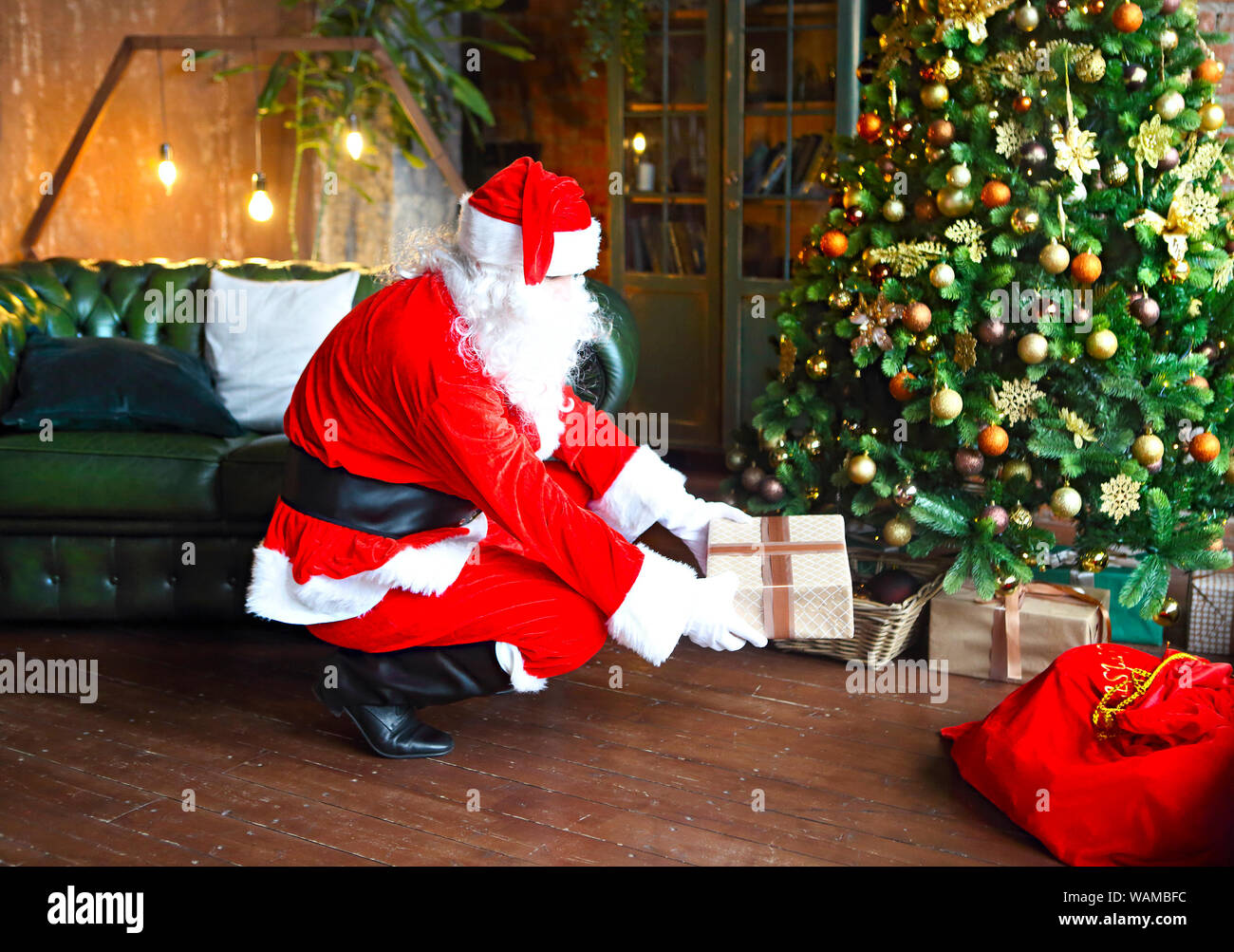 Santa Claus secretly putting gift boxes under the Christmas tree. Xmas Stock Photo