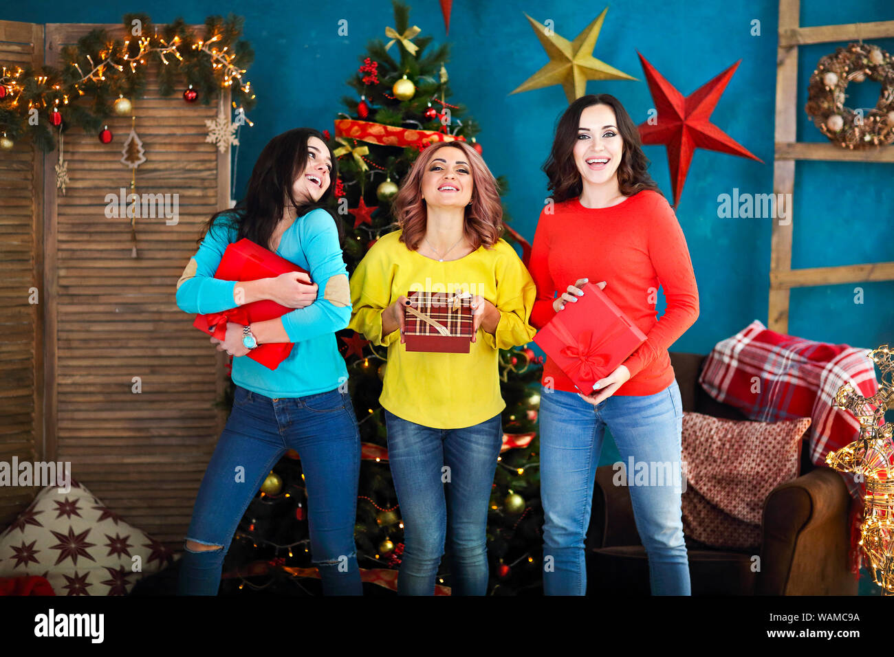 Smiling happy woman with gift box over living room on Christmas tree background. Holidays and people concept. Xmas time Stock Photo