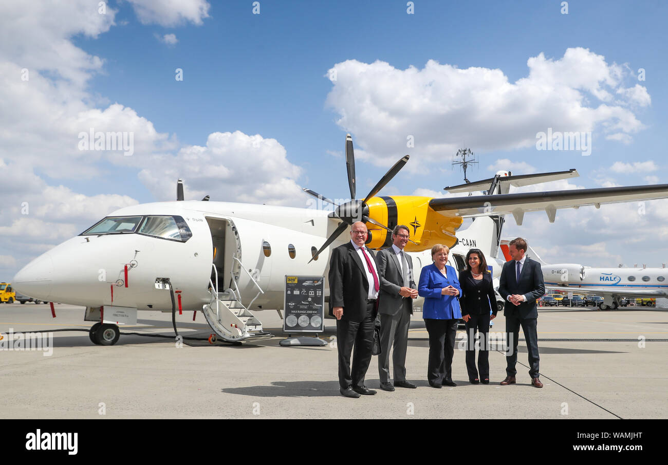 21 August 2019, Saxony, Schkeuditz: Peter Altmaier (CDU, l-r), Federal Minister of the Environment, Andreas Scheuer (CSU), Federal Minister of Transport, Angela Merkel, Federal Chancellor (CDU), Eren Ozmen, owner of the Sierra Nevada Corporation, and Michael Kretschmer, Prime Minister of Saxony (CDU), are standing in front of a Dornier 328 before the first National Aviation Conference at Leipzig-Halle Airport. Guiding principle of the conference: The German aviation industry should become more competitive and at the same time more environmentally friendly. Among those expected are the Federal Stock Photo