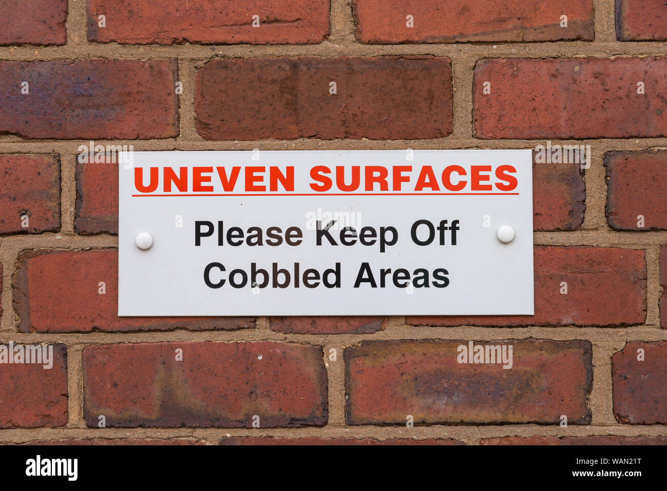 Sign saying uneven surfaces please keep off cobbled areas fixed to brick wall Stock Photo