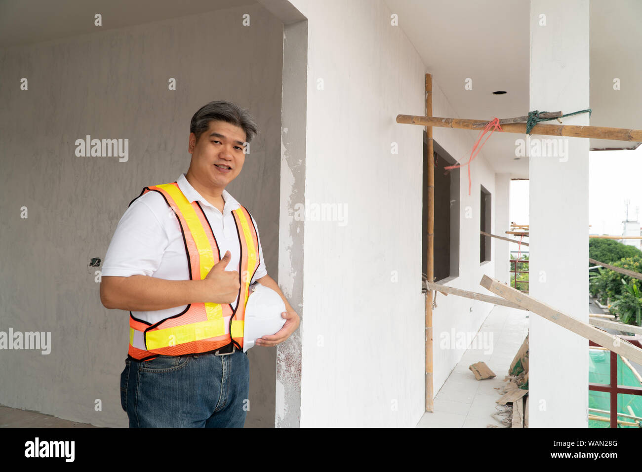 Asian professional engineer workering in house construction site for inspection of the cottage under construction and lift the thumb up. Stock Photo