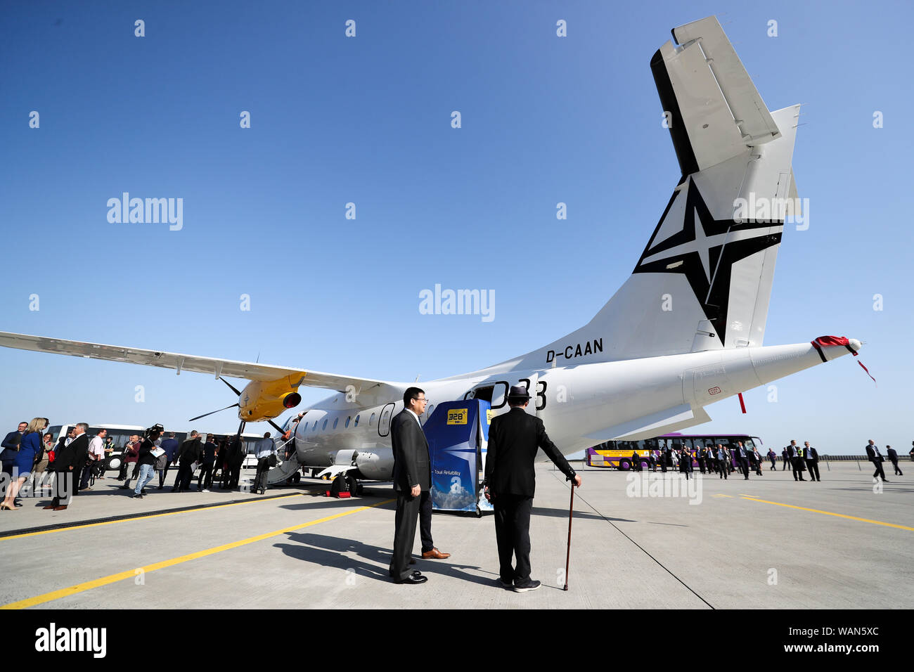 Schkeuditz, Germany. 21st Aug, 2019. Guests of the National Aviation Conference are standing in front of one (Dornier 328) at Leipzig-Halle Airport. Guiding principle of the conference: The German aviation industry should become more competitive and at the same time more environmentally friendly. Among those expected are the Federal Chancellor, the Minister of Transport, the Minister of Economics and the CEO of Lufthansa. Discussions are also likely to take place about the air traffic tax. Credit: Jan Woitas/dpa-Zentralbild/dpa/Alamy Live News Stock Photo