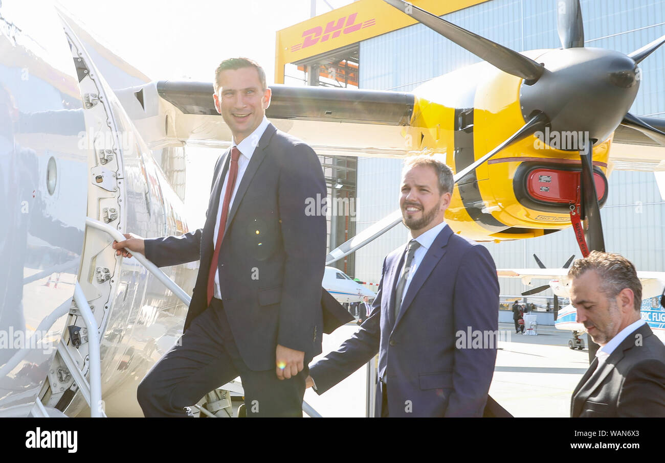 21 August 2019, Saxony, Schkeuditz: Martin Dulig, Economics Minister of Saxony (SPD, l), and Nico Neumann, Production Director at 328 Support Service (M), climb a Dornier 328 at Leipzig-Halle Airport. The US-American company Sierra Nevada Corporation (SNC) plans to build the further development Dornier D328NEU as an aircraft with 39 seats in Leipzig in the future. Its predecessor, the Dornier 328 Turboprop propeller aircraft, was developed in the 1980s in Oberpfaffenhofen, Bavaria. It was the last airplane developed in Germany. At the end of 2023 the first plane is to go into service, the plan Stock Photo