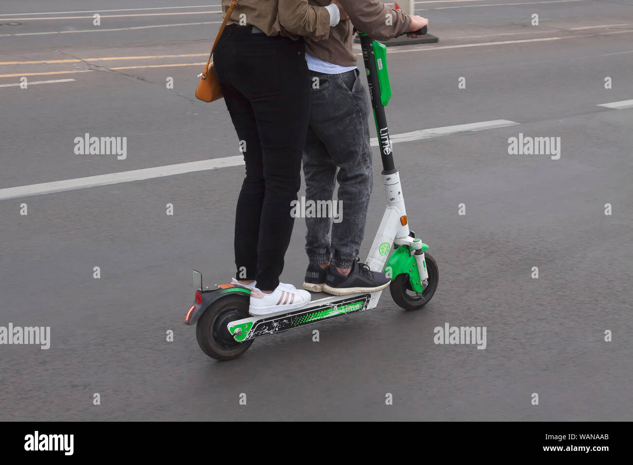 Two persons on an e-scooter, not allowed Stock Photo