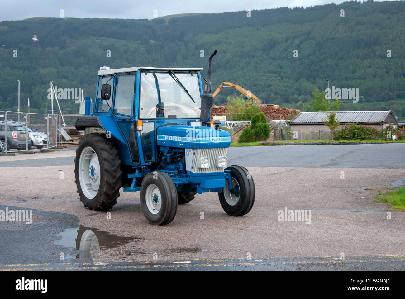 Man Driving 1984 Blue White Ford 3910 Model Tractor With Cab