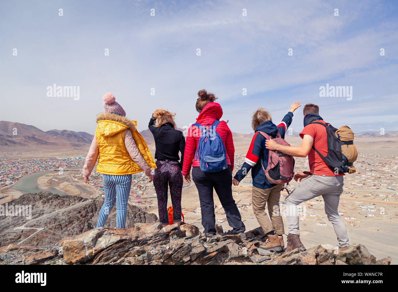 Mongolia Ulgii 2019-05-04 Tourist group in colored clothes with backpacks hiking, climbing, walking together with guide standing on mountain top, view Stock Photo
