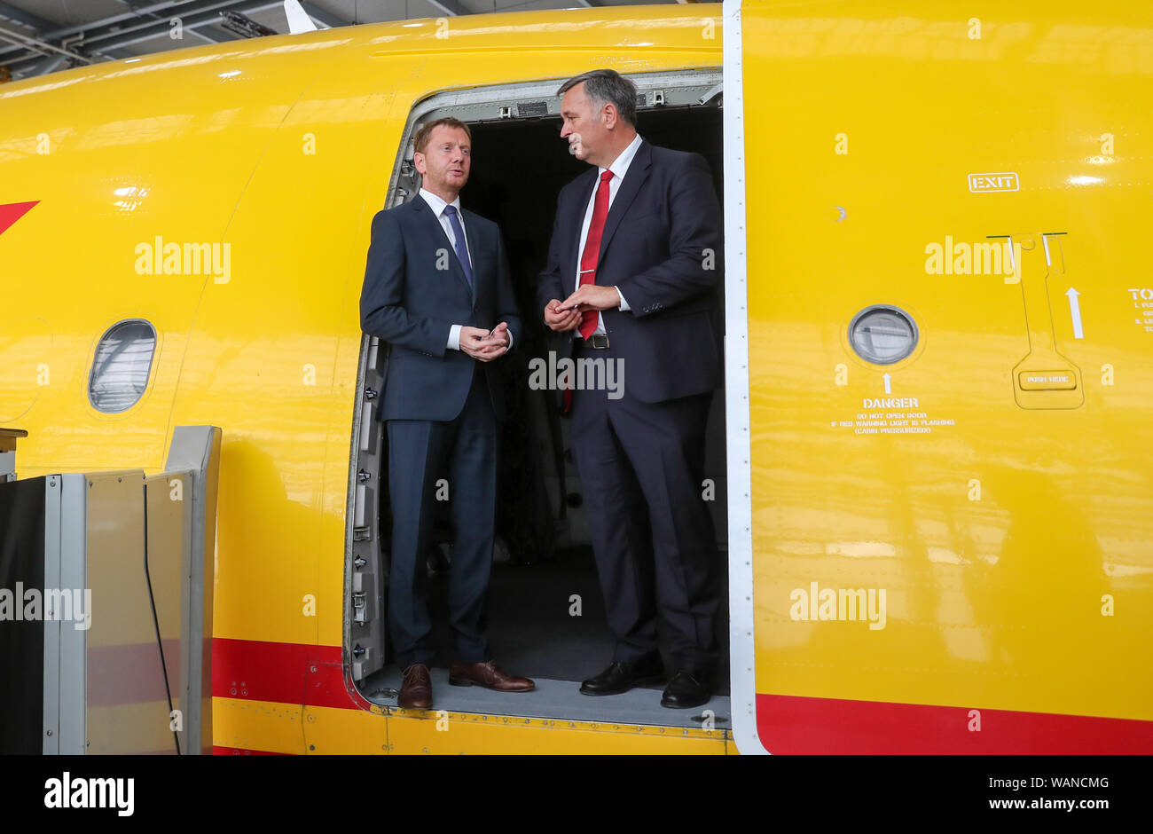Schkeuditz, Germany. 21st Aug, 2019. Michael Kretschmer (CDU, l), Prime Minister of Saxony, stands next to Markus Otto, Managing Director of DHL Leipzig, on the sidelines of the National Aviation Conference in the door of a cargo aircraft at Leipzig-Halle Airport. Credit: Jan Woitas/dpa-Zentralbild/dpa/Alamy Live News Stock Photo