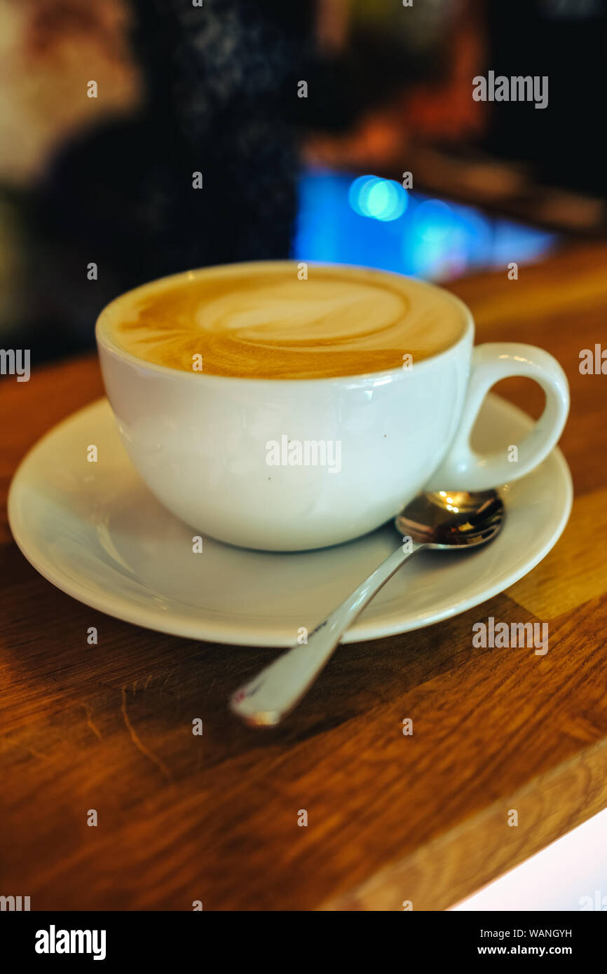 Cappuccino on wooden table with warm lighting Stock Photo