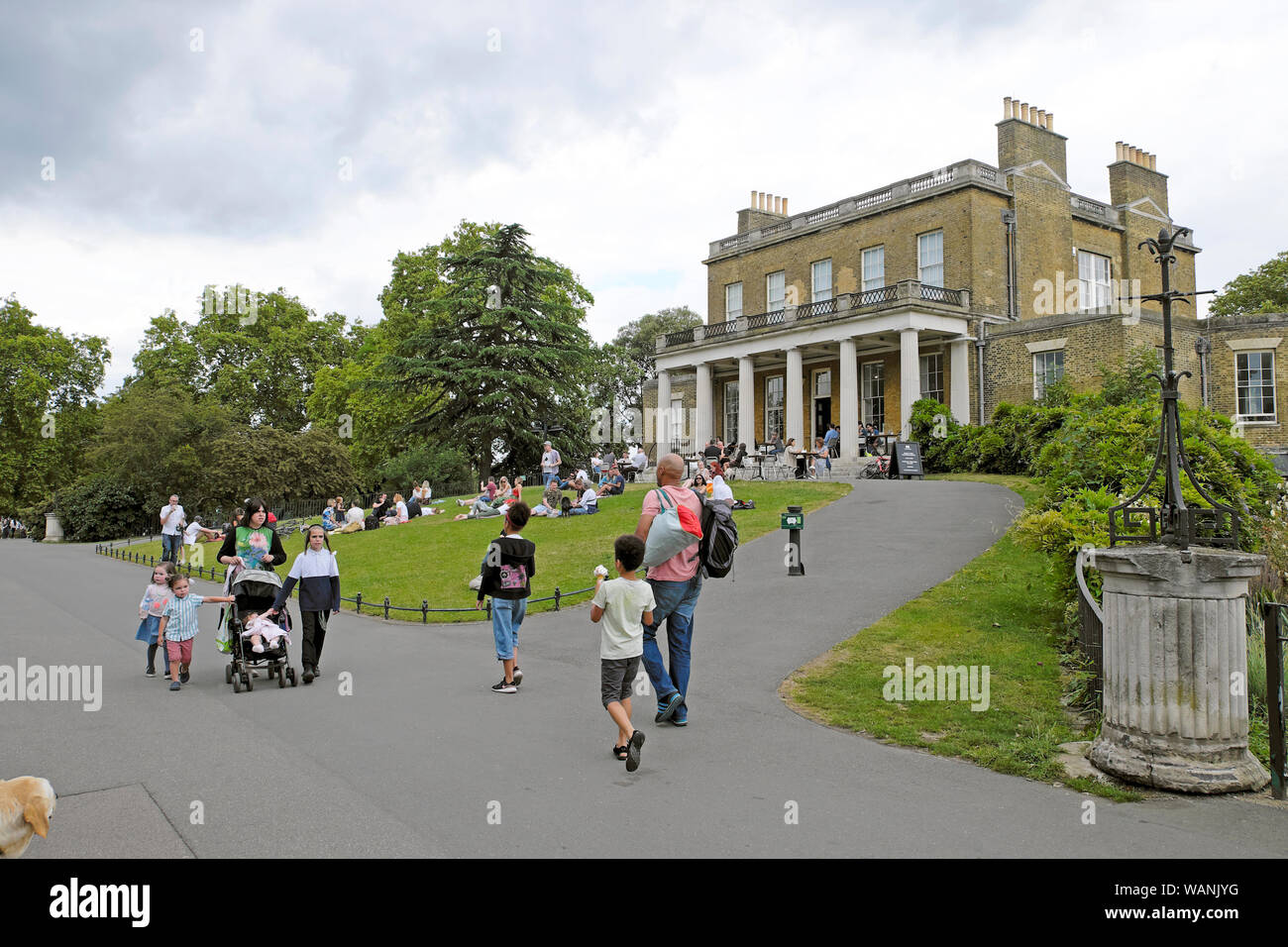 Families strolling along the path outside Clissold House and sitting on the lawn in Clissold Park in summer Stoke Newington London UK  KATHY DEWITT Stock Photo