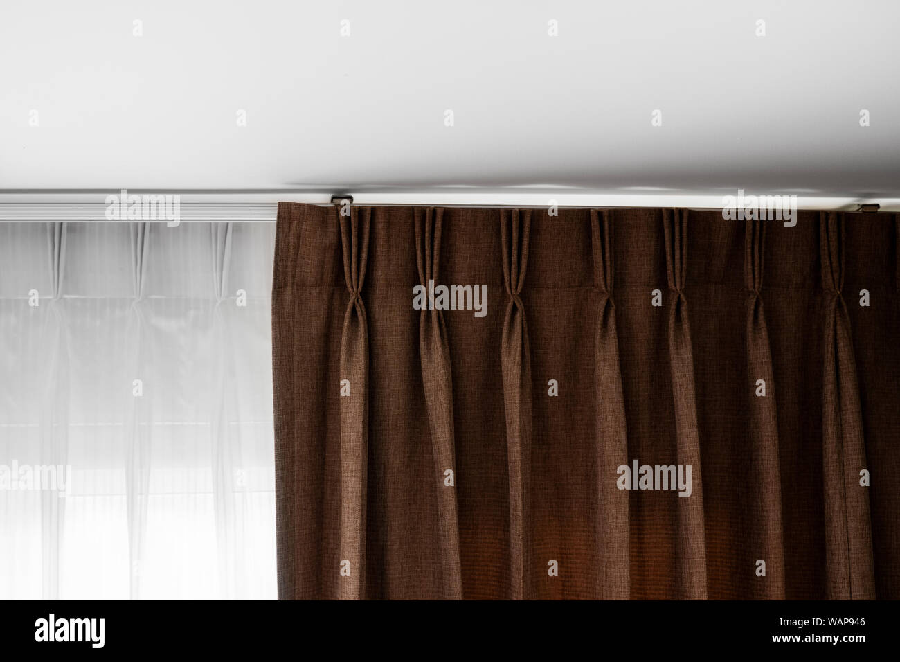 Brown Curtains And White Tulle On A Rail With A White