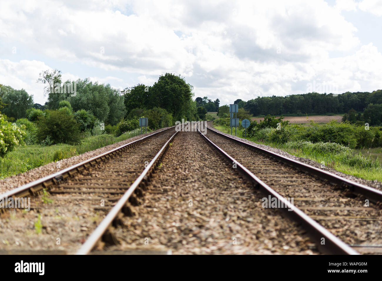 An empty train track, there are 2 tracks leading to a point on the horizon in rural countryside Stock Photo