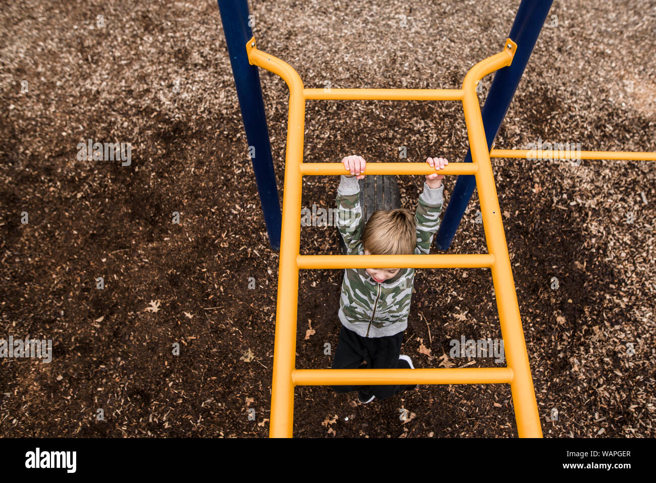 looking down from above at young boy going across monkey bars at park Stock Photo