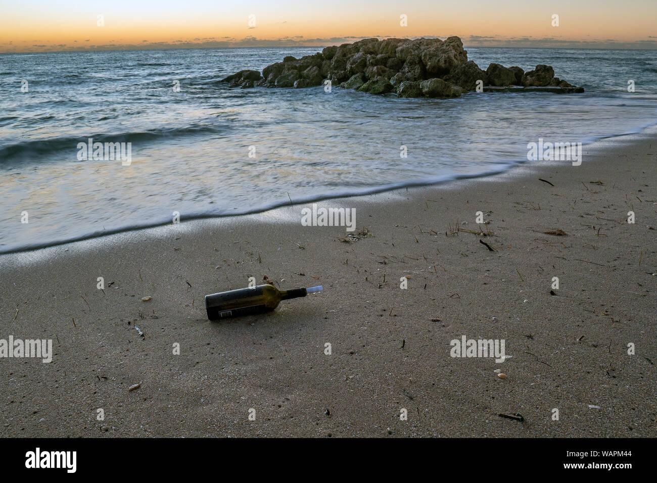 Wine bottle with a rolled up piece of paper washed up on a sandy beach. Stock Photo