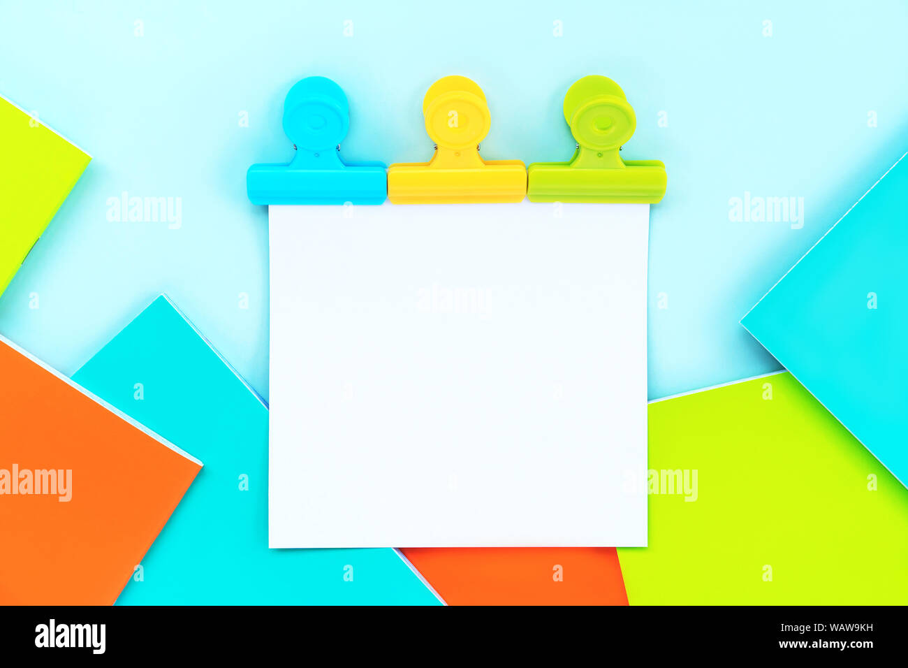 A white sheet for writing attached by three multi-colored stationery clips  Stock Photo