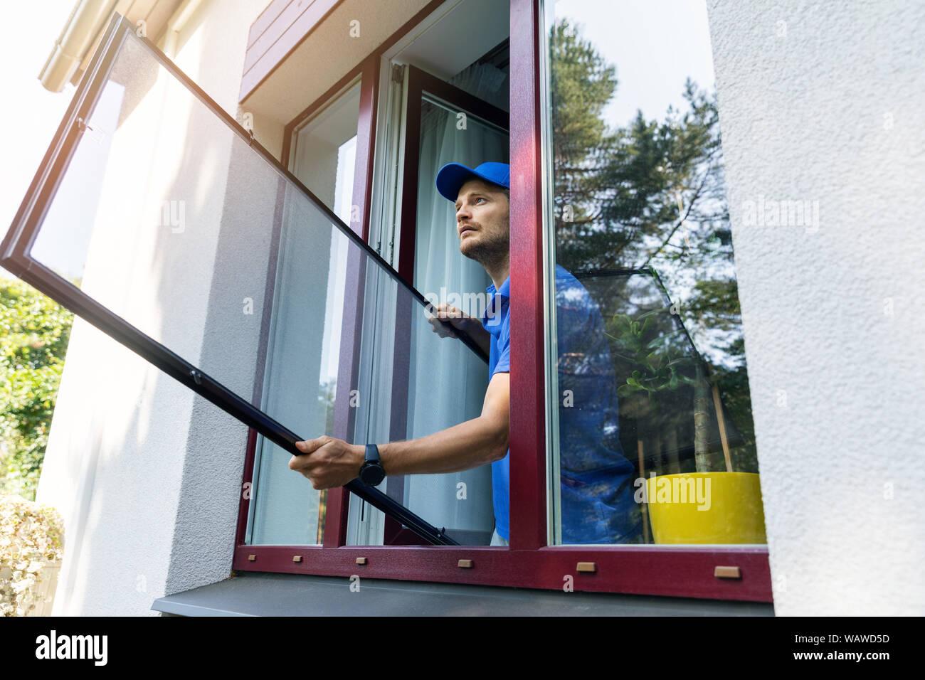 handyman installing mosquito net mesh screen on house window