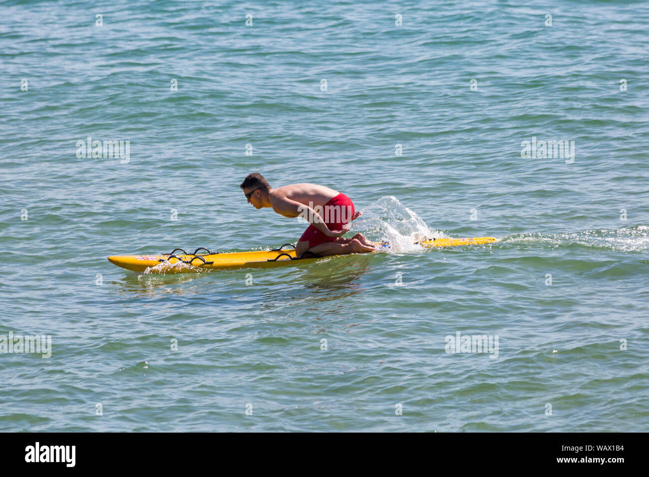 Bournemouth, Dorset UK. 22nd Aug 2019. UK weather: a lovely warm sunny day as beachgoers head to the seaside at Bournemouth beaches to enjoy the sunshine, as temperatures are set to get higher for the Bank Holiday weekend. RNLI Lifeguard on surf board. Credit: Carolyn Jenkins/Alamy Live News Stock Photo