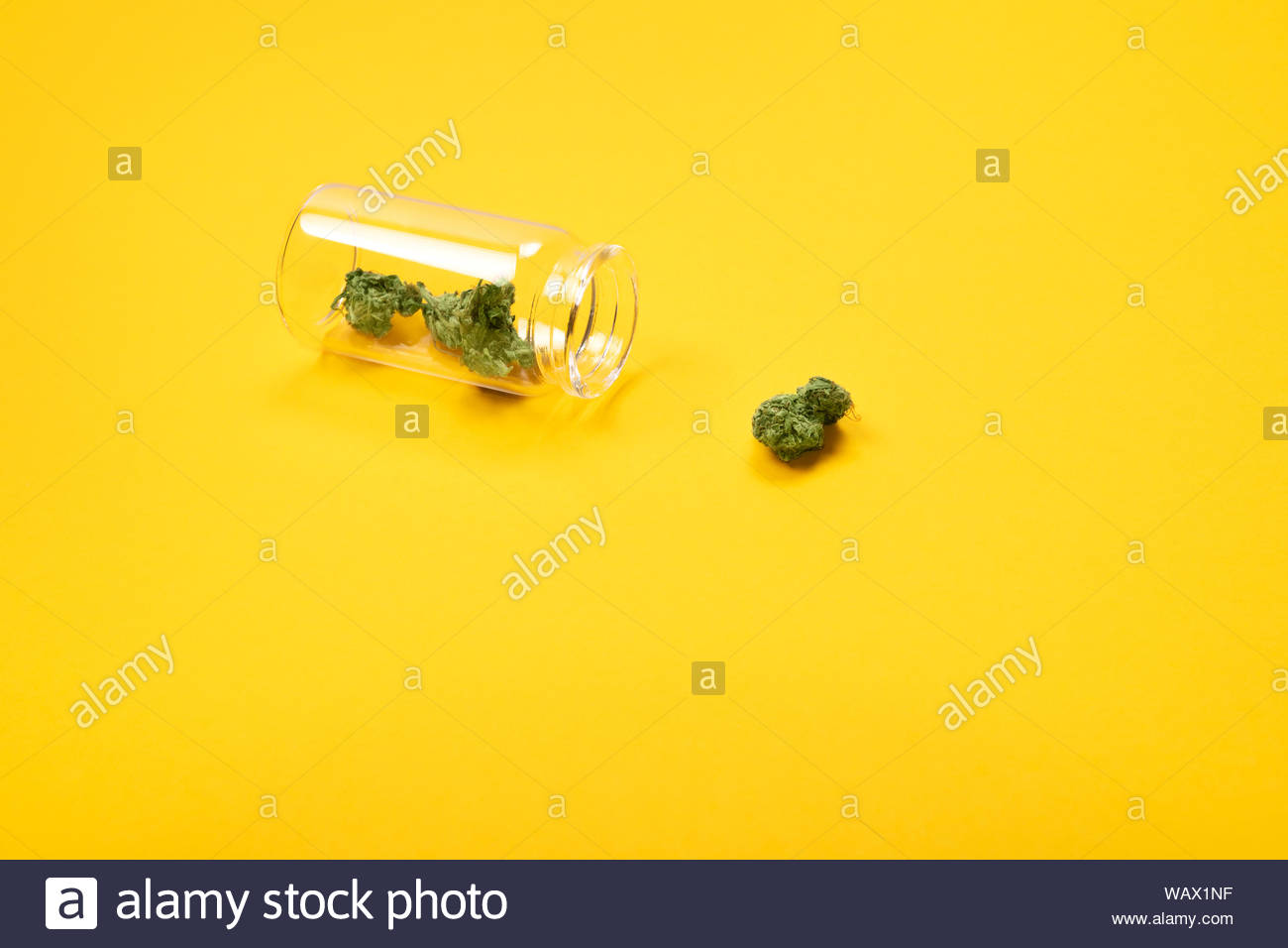 Dried medical marijuana buds in a small open glass jar and scattered aside on yellow background. Alternative treatment. Medical cannabis.Place for tex Stock Photo