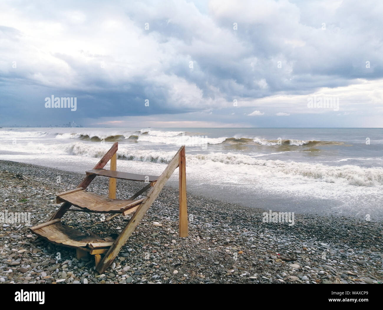 Old, broken wooden staircase in a cloudy sky, against the backdrop of raging sea, waves, ocean storm, thunderstorm, natural disaster. City in the back Stock Photo