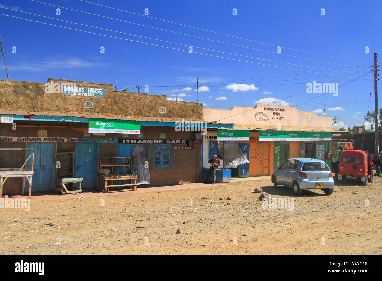 Village street, Kenya, East Africa. Local people outside small shops under blue skies. Authentic Africa, travel by Road Stock Photo