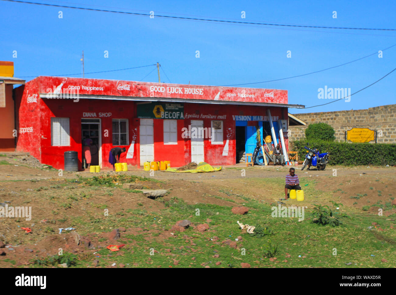 """Small shops at side of road, Kenya, East Africa. Local people outside selling water containers on hot day. Shop named """"Good Luck house"""" Stock Photo"""