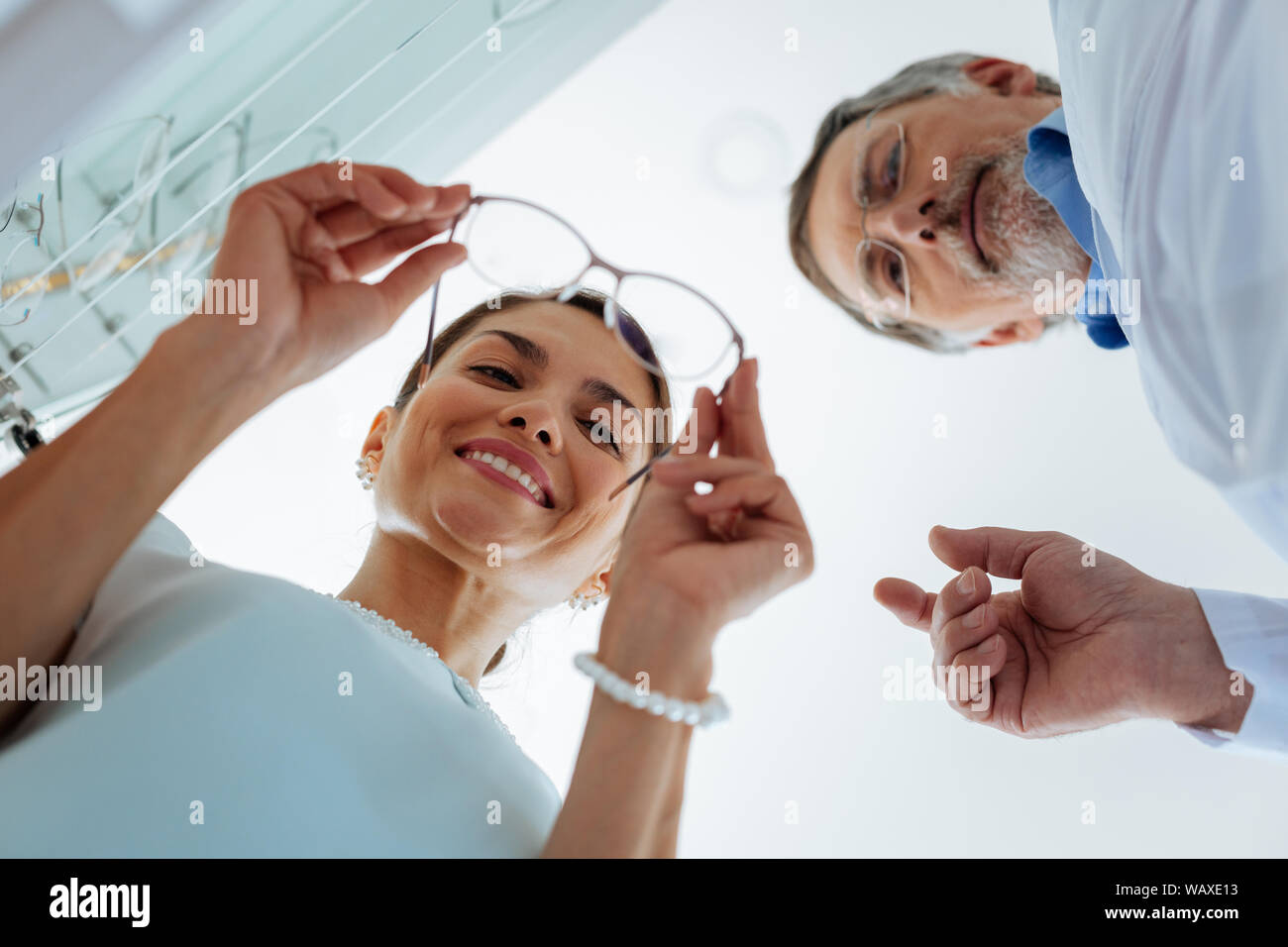 Low angle of a nice positive woman standing near the optician Stock Photo
