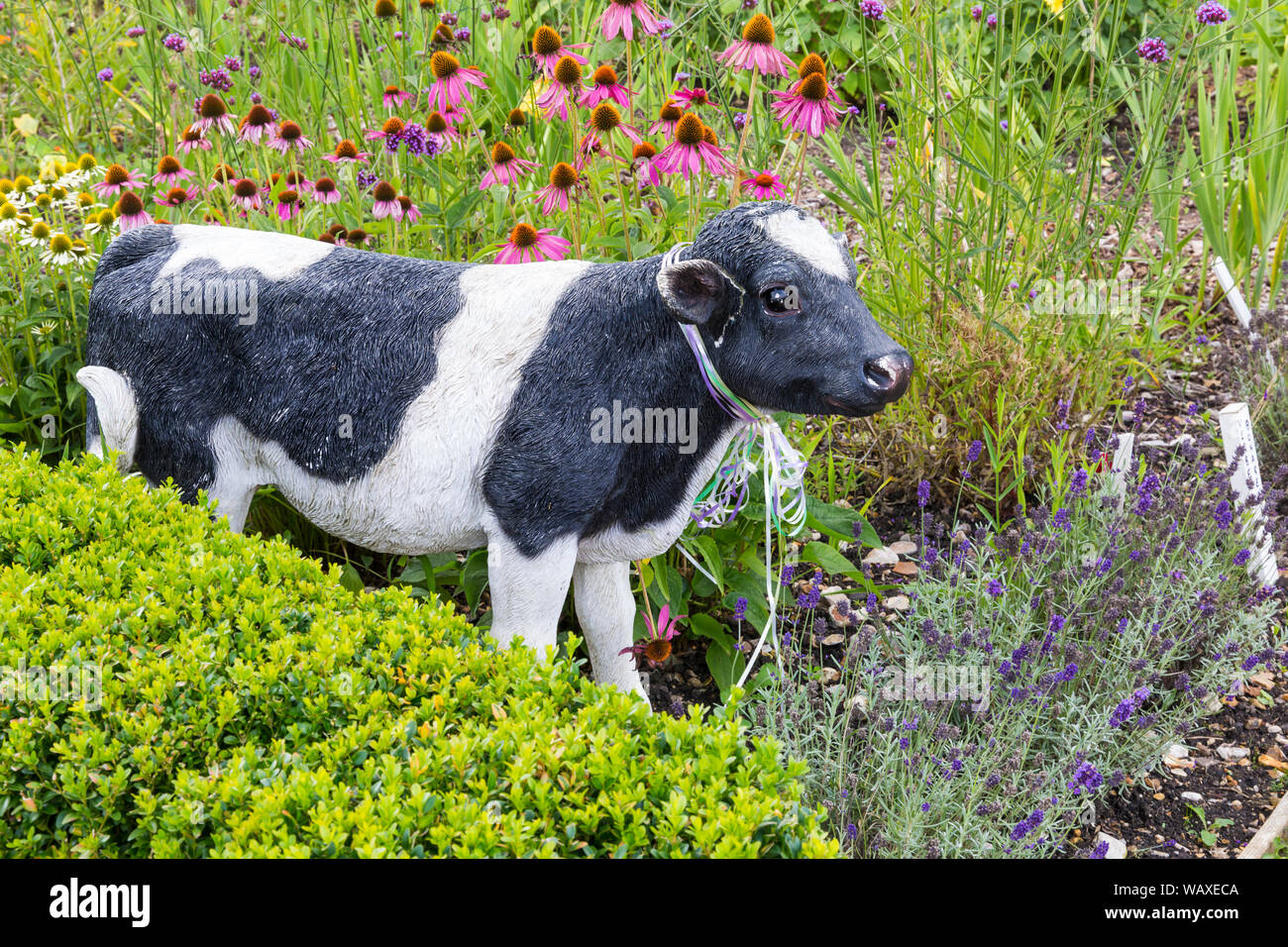 Cow ornament among the flowers at Patrick's Patch, Beaulieu, New Forest, Hampshire UK in August Stock Photo